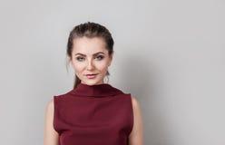 Le portrait des affaires de port de jolie jeune femme vêtx regarder l'appareil-photo avec le sourire, se tenant contre le mur gri photo stock