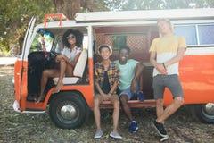 Le portrait des amis avec le camping-car s'est garé au terrain de camping Photo stock