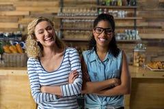 Le portrait des amis féminins se tenant avec des bras a croisé près du compteur Photos libres de droits