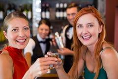 Le portrait des amis heureux tenant une tequila a tiré devant le compteur de barre Photos libres de droits