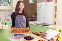 Le portrait des biscuits femelles et des gâteaux de cuisson de chef se tenant souriants à l'apparence d'appareil-photo frais-a fa images libres de droits