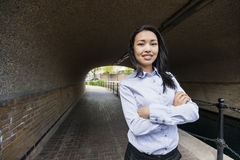 Le portrait des bras debout de femme d'affaires asiatique sûre a croisé sous le pont Photos stock