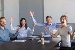Le portrait des collègues enthousiastes soulèvent des mains vers le haut d'heureux avec le succès image stock