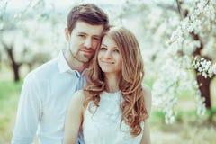 Le portrait des couples affectueux dans le pommier de floraison font du jardinage Projectile horizontal image stock