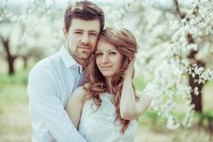 Le portrait des couples affectueux dans le pommier de floraison font du jardinage Projectile horizontal photos stock