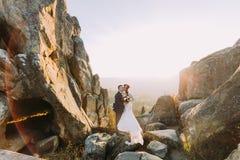 Le portrait des couples enloved romantiques de nouveaux mariés dans le coucher du soleil s'allume sur le paysage majestueux de mo Image stock