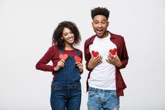 Le portrait des couples gais d'afro-américain tenant le coeur de papier rouge ont plaisir à jouer la position au-dessus du fond g Image libre de droits