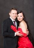 Le portrait des couples heureux dans l'amour posant au studio sur le fond gris s'est habillé en rouge. Image libre de droits