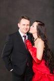 Le portrait des couples heureux dans l'amour posant au studio sur le fond gris s'est habillé en rouge. Photos stock