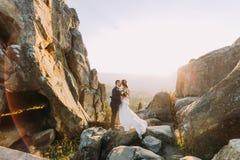 Le portrait des couples romantiques de nouveaux mariés dans le coucher du soleil jaune s'allume sur le paysage majestueux de mont Image stock