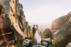 Le portrait des couples romantiques de nouveaux mariés dans le coucher du soleil s'allume sur le paysage majestueux de montagne a Photos stock