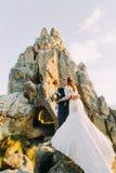 Le portrait des couples romantiques de nouveaux mariés dans le coucher du soleil s'allume sur le paysage majestueux de montagne a Images stock