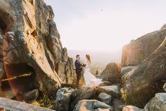Le portrait des couples romantiques de nouveaux mariés dans le coucher du soleil s'allume sur le paysage majestueux de montagne a Photo libre de droits