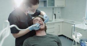 Le portrait des dentis d'une femme et son type charismatique patient dans une salle dentaire ont une procédure d'hygiène buccale banque de vidéos