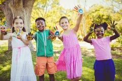 Le portrait des enfants mignons avec composent avoir coloré des mains Photos stock