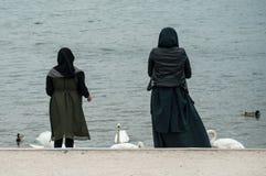Le portrait des femmes musulmanes de retour regardent railler le pain au canard et au cygne dans le lac de frontière photographie stock libre de droits