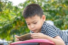 Le portrait des garçons asiatiques jouent des téléphones portables en parc photo stock