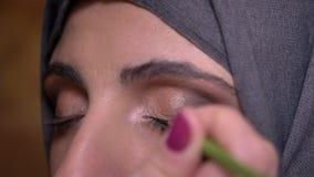Le portrait des mains faisant le maquillage d'oeil et dessinant la flèche noire pour la belle dame musulmane dans le hijab bricke banque de vidéos