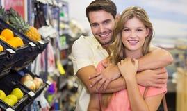 Le portrait des produits alimentaires de achat de sourire de couples lumineux arment autour Photos stock