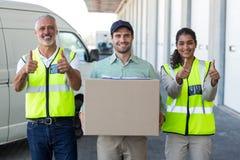 Le portrait des travailleurs posent avec des pouces près d'un livreur Photographie stock libre de droits