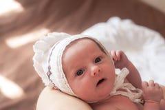 Le portrait du bébé nouveau-né dans le chapeau blanc se trouvant sur des mères remettent photos libres de droits