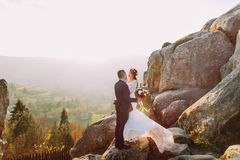 Le portrait du baiser romantique de couples de nouveaux mariés dans le coucher du soleil s'allume sur le paysage majestueux de mo Photo libre de droits