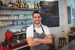Le portrait du barman sûr avec des bras a croisé au café Photo stock
