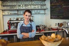 Le portrait du barman sûr avec des bras a croisé au cafétéria Photo stock