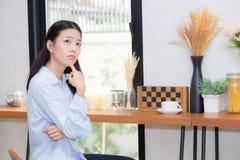 Le portrait du beau jeune bonheur asiatique de femme et pensent se reposer à la boutique de café photo libre de droits