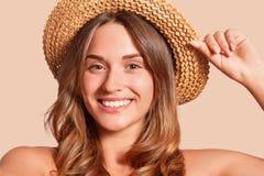 Le portrait du chapeau de paille de port de jolie femme gaie, sembler femelle attrayant souriant directement à la caméra, exprime images libres de droits