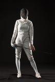 Le portrait du costume de clôture blanc de port de femme sur le noir Photos stock