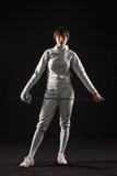 Le portrait du costume de clôture blanc de port de femme sur le noir Photo libre de droits