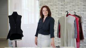Le portrait du couturier mûr de femme regarde la caméra et les sourires dans l'atelier clips vidéos