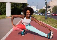Le portrait du jeune étirage sportif de femme d'afro-américain se surpassent photo stock
