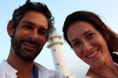 Le portrait du jeune beau couple avec le phare de Cap de Barberia's sur le fond mou, Formentera Photographie stock libre de droits