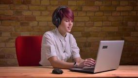 Le portrait du jeune blogger féminin aux cheveux courts dans des écouteurs dactylographiant sur l'ordinateur portable et parlant  clips vidéos