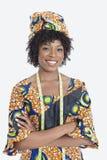 Le portrait du jeune couturier féminin dans des mains debout de vêtement africain d'impression a replié le fond gris Images stock