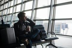 Le portrait du jeune homme bel portant le style occasionnel vêtx se reposer sur le banc de l'aéroport moderne utilisant le smartp Image libre de droits