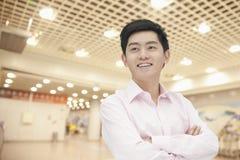 Le portrait du jeune homme d'affaires de sourire sûr dans la chemise de bouton vers le bas avec des bras a croisé, à l'intérieur photo libre de droits