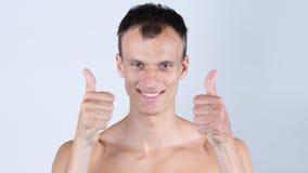 Le portrait du jeune homme sans chemise montre des pouces avec les deux mains photos libres de droits