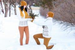 Le portrait du jeune présent d'ami de couples fleurit comme cadeau au gi Images libres de droits