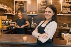 Le portrait du jeune propriétaire de café féminin de sourire, femme sûre avec des bras a croisé la position au compteur avec le f images stock