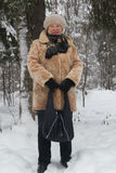 Le portrait du manteau de fourrure supérieur de femme et le chapeau se tenant en hiver froid neigent forêt couverte, se ferment  Photo stock