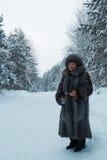 Le portrait du manteau de fourrure supérieur de femme et le chapeau se tenant en hiver froid neigent forêt couverte, verticale Photographie stock