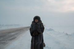 Le portrait du manteau de fourrure supérieur de femme et le chapeau se tenant en hiver froid neigent route couverte, téléobjectif Photo libre de droits