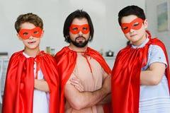 le portrait du père et des fils dans des costumes rouges de super héros avec des bras a croisé regarder la caméra photos stock