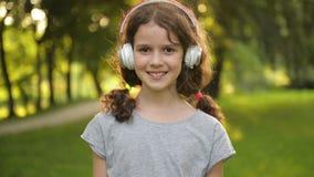 Le portrait du petit étudiant caucasien attirant Girl With Beautiful Brown observe avec des écouteurs Enfant de sourire heureux clips vidéos