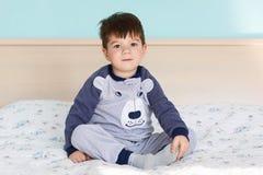 Le portrait du petit enfant adorable dans des pyjamas, repose les jambes croisées au lit confortable dans la chambre à coucher co photos libres de droits
