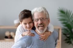 Le portrait du petit-fils heureux ont le grand-p?re sur le dos de sourire d'amusement photos libres de droits