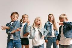 Le portrait du petit garçon et des filles mignons dans des vêtements élégants de jeans regardant la caméra le studio image stock
